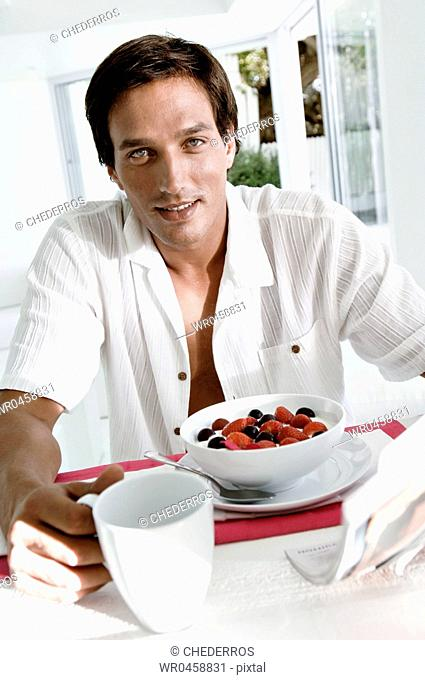 Portrait of a mid adult man sitting at the breakfast table