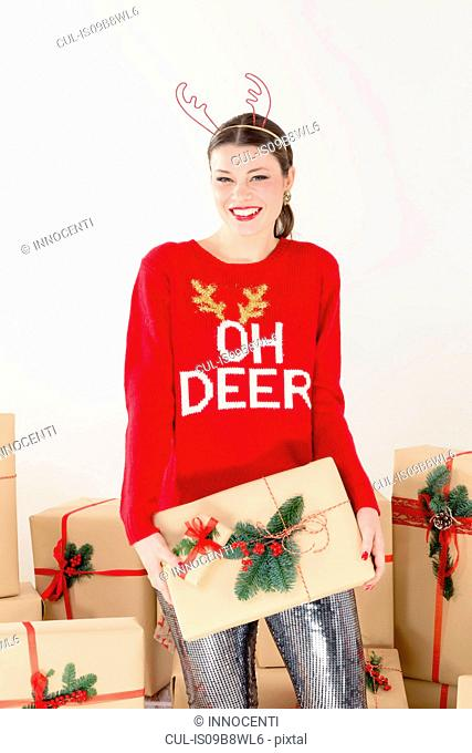 Portrait of young woman in red sweater and reindeer antlers by stacked christmas gifts holding christmas parcel