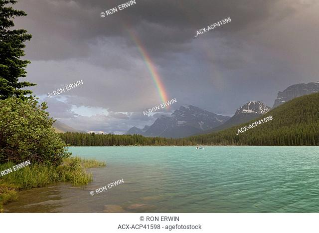 Boats and a canoe with rainbow over Lower Waterfowl Lake, Banff National Park, Alberta, Canada