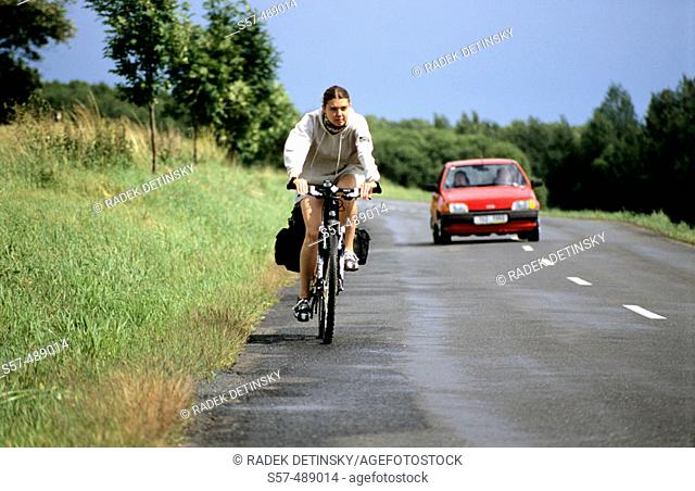 A female cyclist rides her bicycle on a road