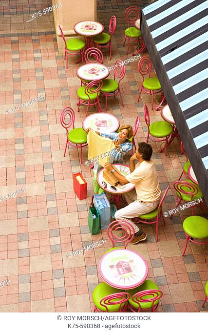 Couple at outdoor cafe with purchases