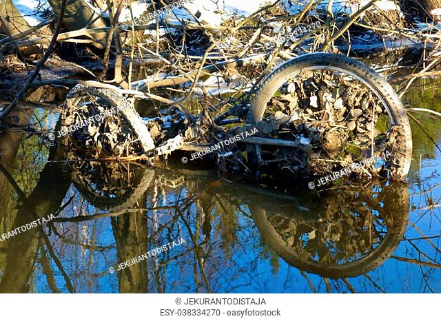 Abandoned rusty bicycle frame and wheels in a small river in Western Helsinki, Finland in late February winter afternoon