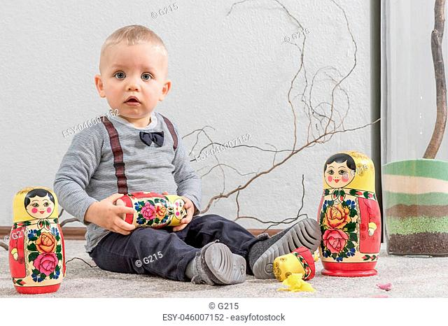 The little boy plays with Russian nested doll