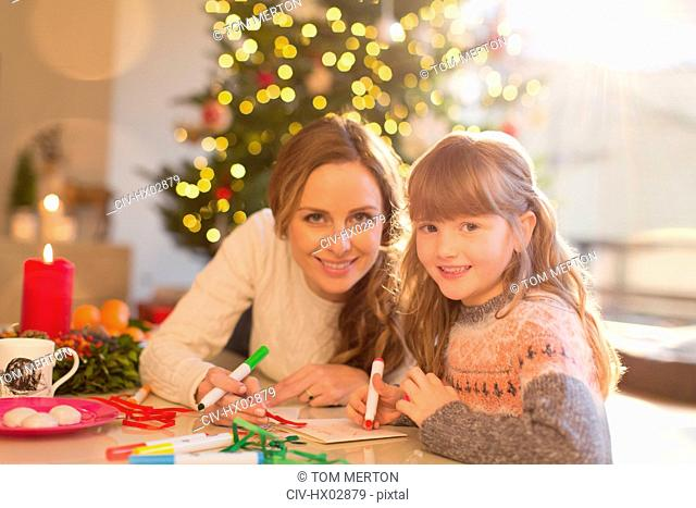 Portrait smiling mother and daughter coloring with markers in Christmas living room