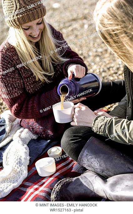 Two girls having a winter picnic on the beach