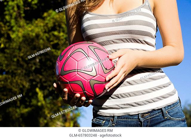 Mid section view of a teenage girl holding a soccer ball