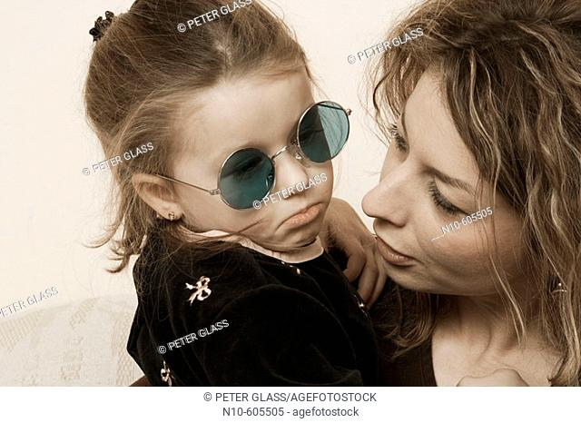 Young girl, wearing sunglasses, sitting with her mother