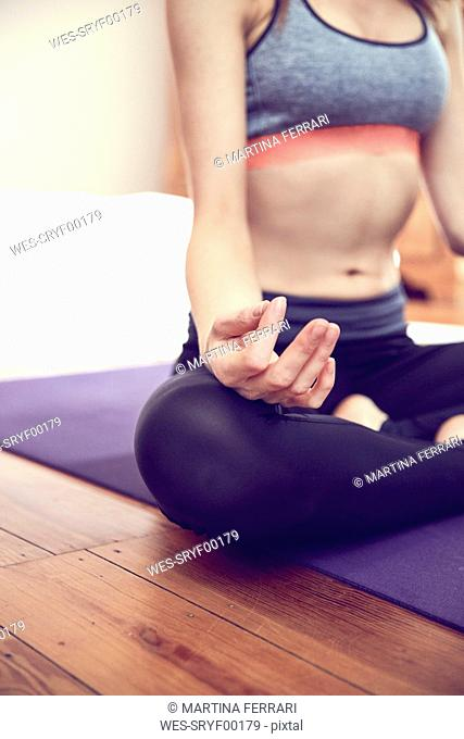 Woman doing yoga exercise at home, partial view