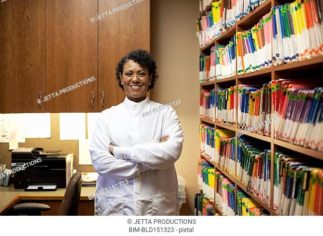 Mixed race dentist standing near medical files in office