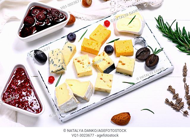 square pieces of camembert cheese, roquefort, cheddar and brie on a white wooden board, next to a raspberry and strawberry jam, top view