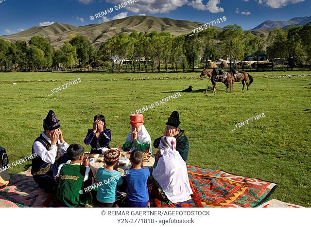 Kazakh family in traditional clothes ending a prayer before a picnic meal in pastureland at Saty Kazakhstan
