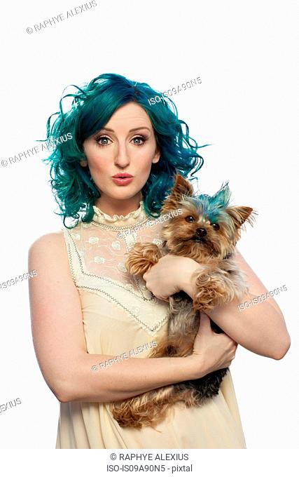 Young woman with green hair holding Yorkshire terrier, portrait