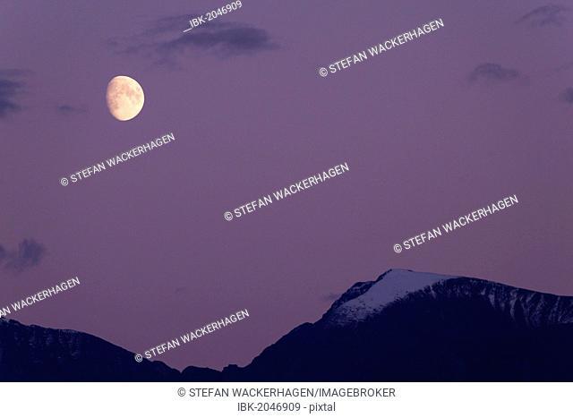 Moon over mountain top, twilight, Yukon Territory, Canada