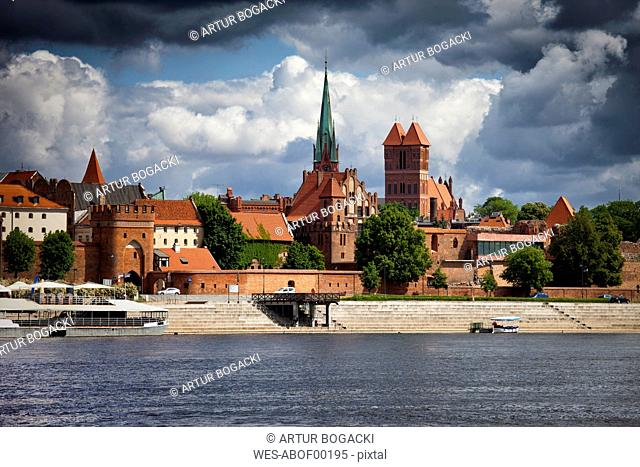 Poland, Torun, view to city skyline with Vistula River in the foreground