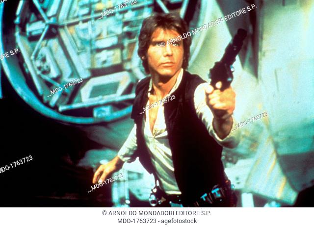 Harrison Ford drawing a gun. In a scene from George Lucas' epic space opera Star Wars, the American actor Harrison Ford as rebel smuggler Han Solo draws a gun...