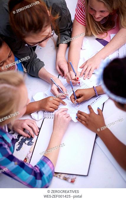 Teacher and schoolgirls writing on paper