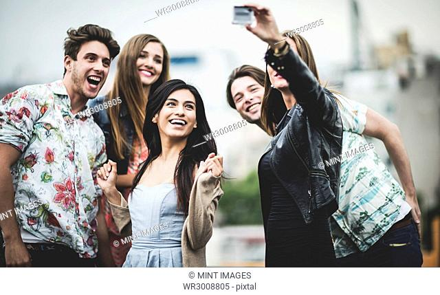 A group of five young people standing on a rooftop posing for a selfie