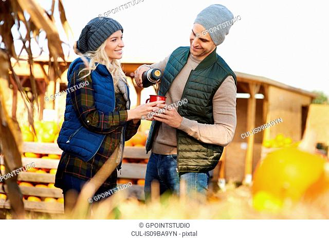 Couple pouring coffee from flask at pumpkin patch