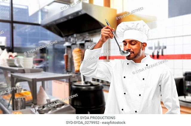 indian chef tasting food from ladle at kebab shop