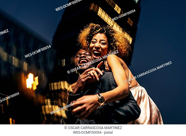 Laughing young couple having fun at night in the city