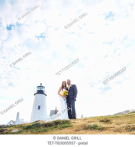 Portrait of married couple, lighthouse in background