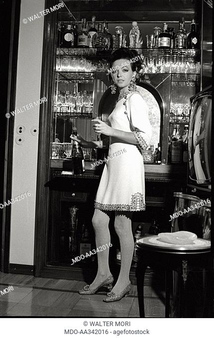 Portrait of Bedy Moratti in her house. The Italian actress Bedy Moratti posing for a portrait at her home's bar corner. Milan, May 1968