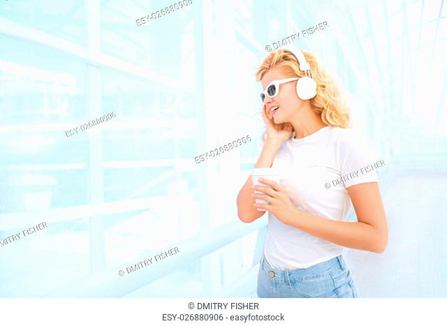 Beautiful young woman in sunglasses with music headphones, standing on the bridge with a take away coffee cup and smiling