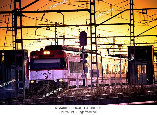 Renfe train in a station at sunset. Maresme, Catalonia, Spain