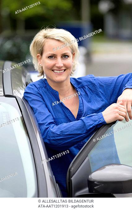 Female car driver stands on opened door