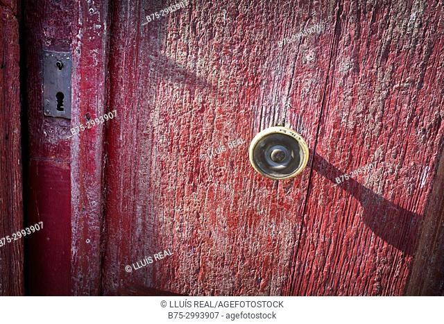 Close-up of the knob of an old door with flaking red paint. Santo-Pietro-di-Tenda, Corsica, France