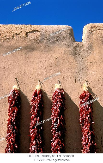 Large chili ristras on adobe wall at the entrance to the Martinez Hacienda (circa 1804), Taos, New Mexico USA