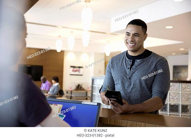 Smiling male patient paying insurance copayment with credit card reader at clinic check-in counter