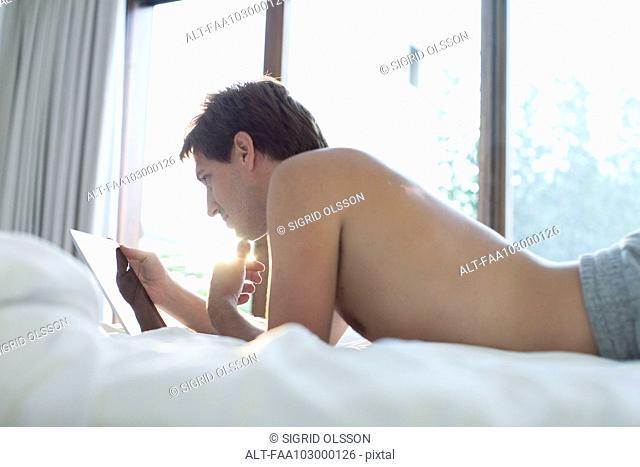 Man lying in bed using digital tablet