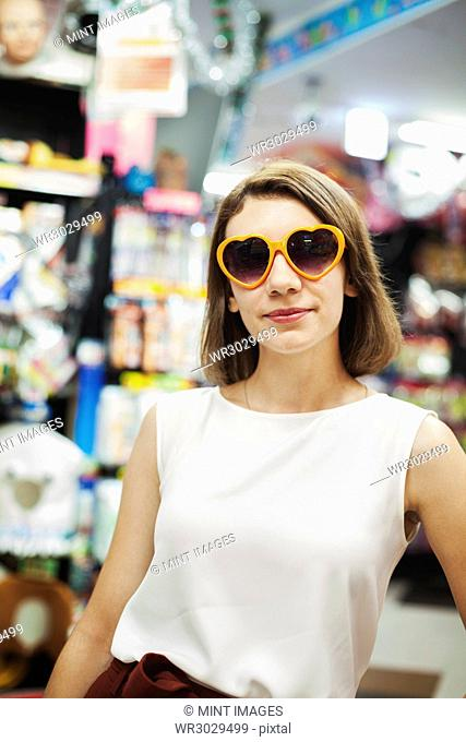 Young woman with brown hair wearing white sleeveless top wearing orange heart shaped sunglasses, looking at camera
