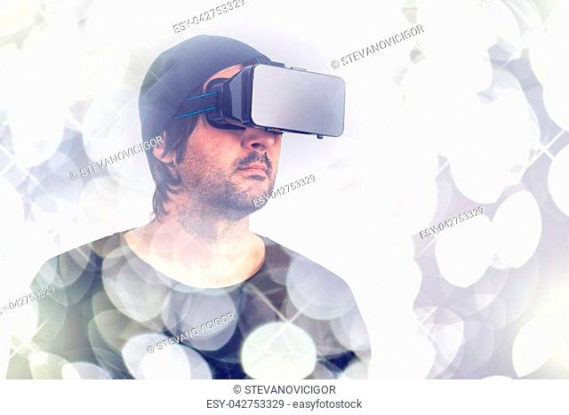 Male actor immersed in experience of virtual reality environment wearing vr goggles, augmented-reality headset, and enjoying 3d cyberspace multimedia content