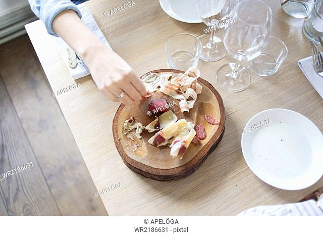 High angle view of woman's hand holding cold cut at outdoor restaurant