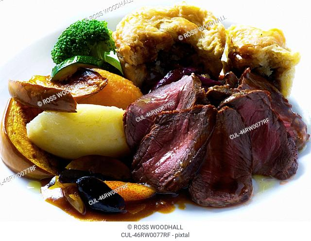 Plate of roast venison with beef pudding