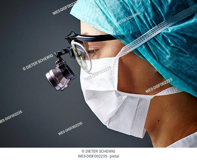 Young doctor wearing mask and magnifying spectacles