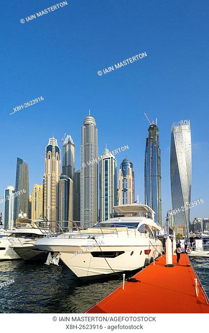 Luxury motor yachts on display with skyline of skyscrapers at the Dubai International Boat Show 2016