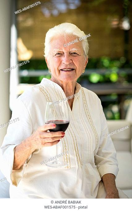 Portrait of smiling senior woman with glass of red wine