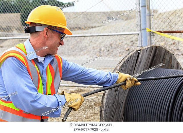 Electrical engineer pulling power cable from reel