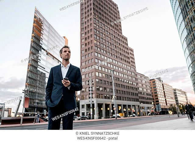 Germany, Berlin, businessman with smartphone standing at Potsdamer Platz