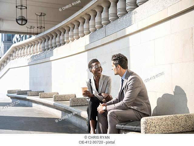 Corporate businessman and businesswoman enjoying coffee break on sunny stairs