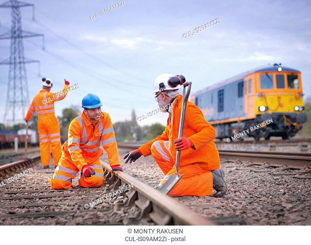 Apprentice railway worker instructed by engineer on railway