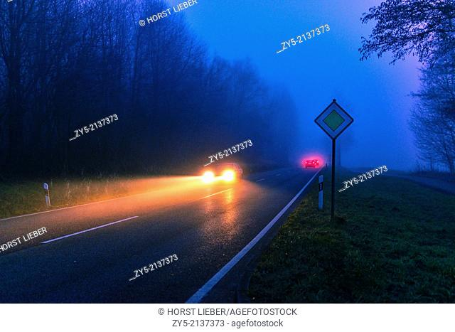 Dangerous road traffic situation in fog and rain. The cars are driving too fast on a wet slippery road on a rural road in Germany