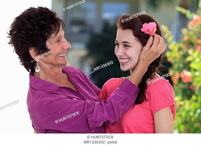 Senior woman smiling adjusting flower in granddaughter's hair