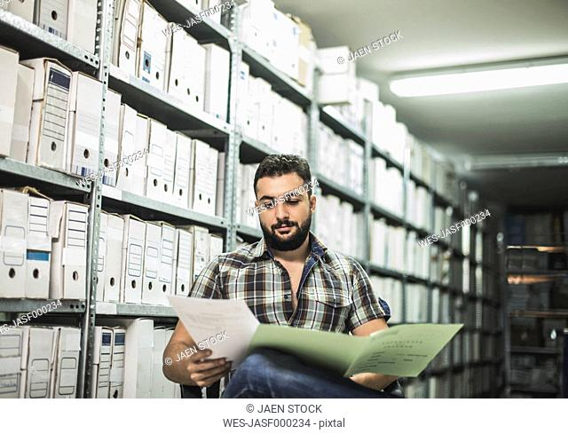 Bearded man working on file in an archive