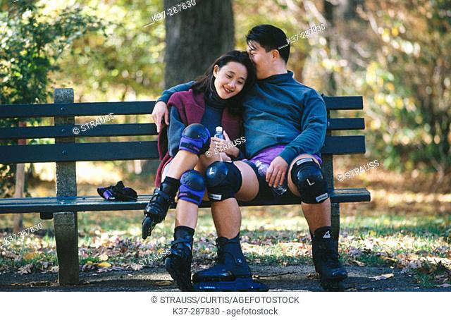 Affectionate asian couple sitting on park bench after rollerblading, wearing knee pads and roller blades