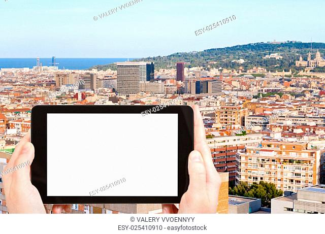 travel concept - tourist photograph Barcelona city and hill Montjuic, Spain in evening on tablet pc with cut out screen with blank place for advertising logo