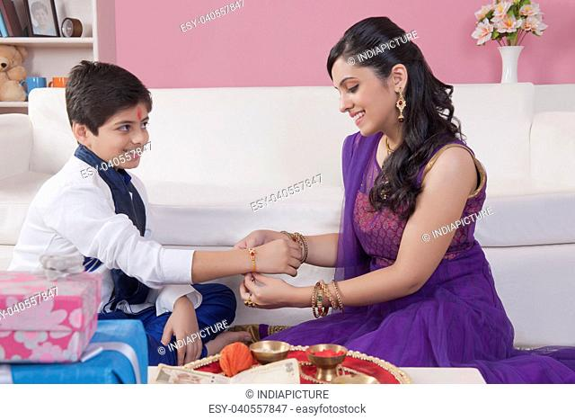 Sister tying rakhi on her brother wrist